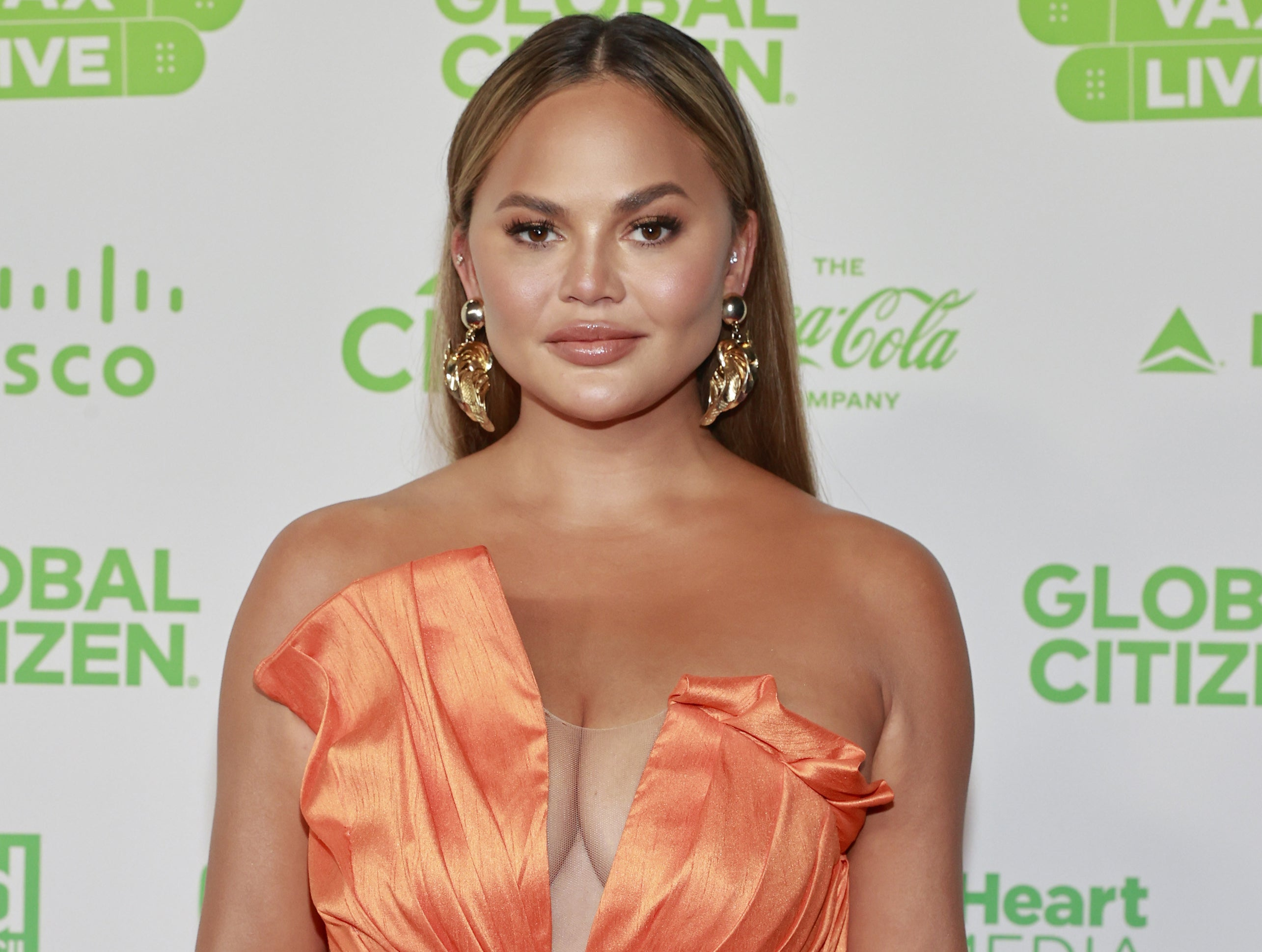 Chrissy wears a strapless orange dress to a recent event