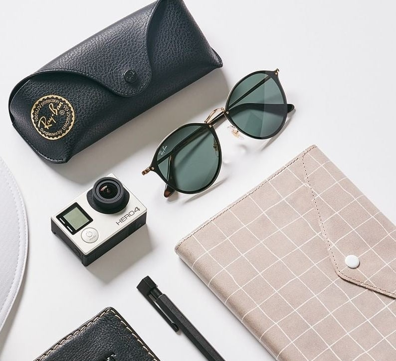 A pair of shades next to a glasses case, a small camera, and a notebook