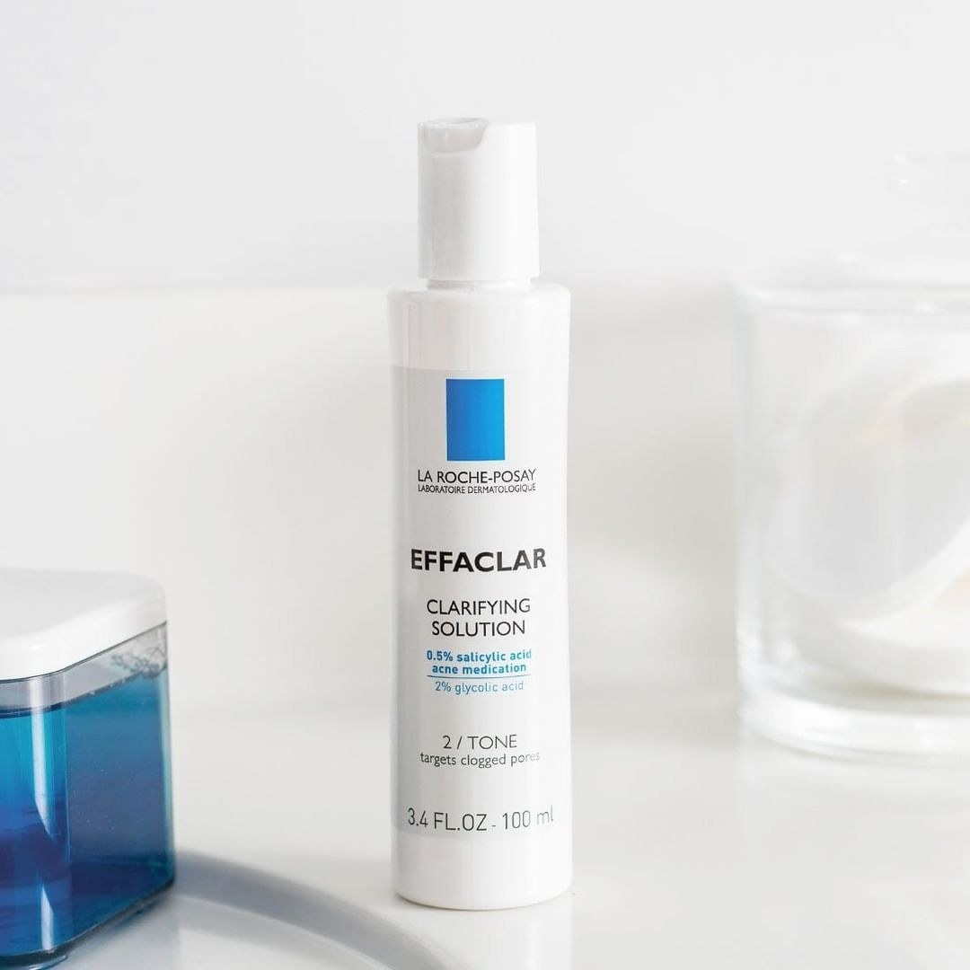 Bottle of Effaclar against white background near jars of liquid
