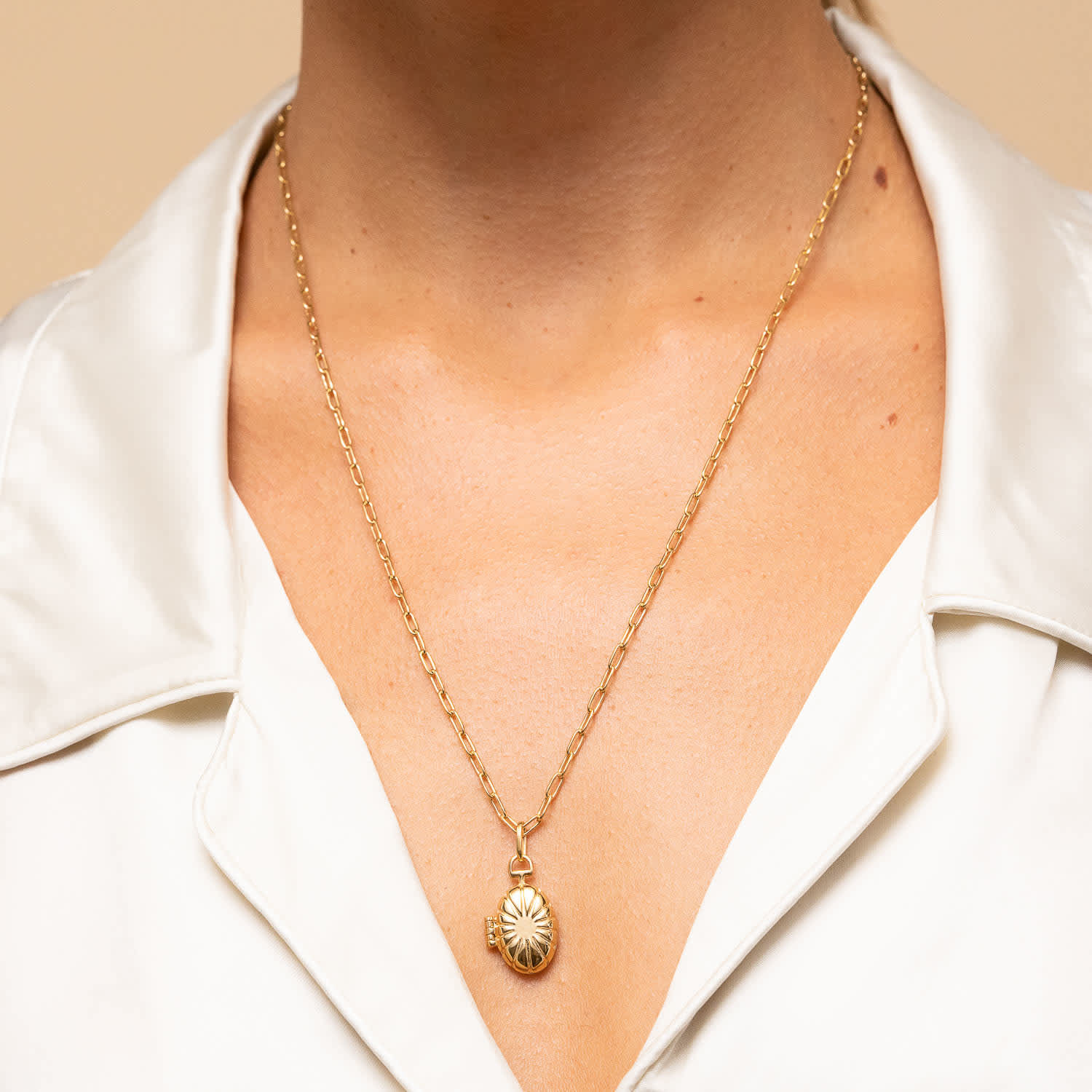A person wearing a locket necklaces