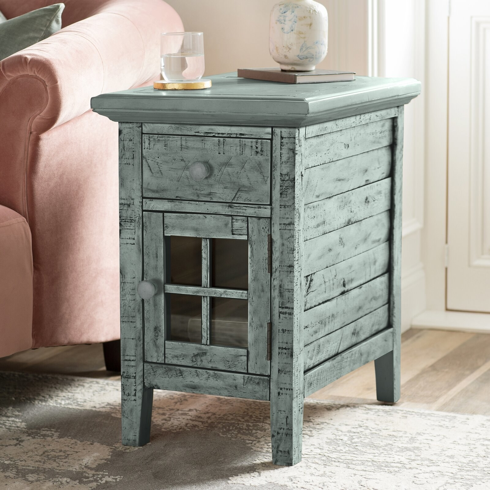 The end table, which has a glass-paneled cabinet door and a closed drawer, in blue-green