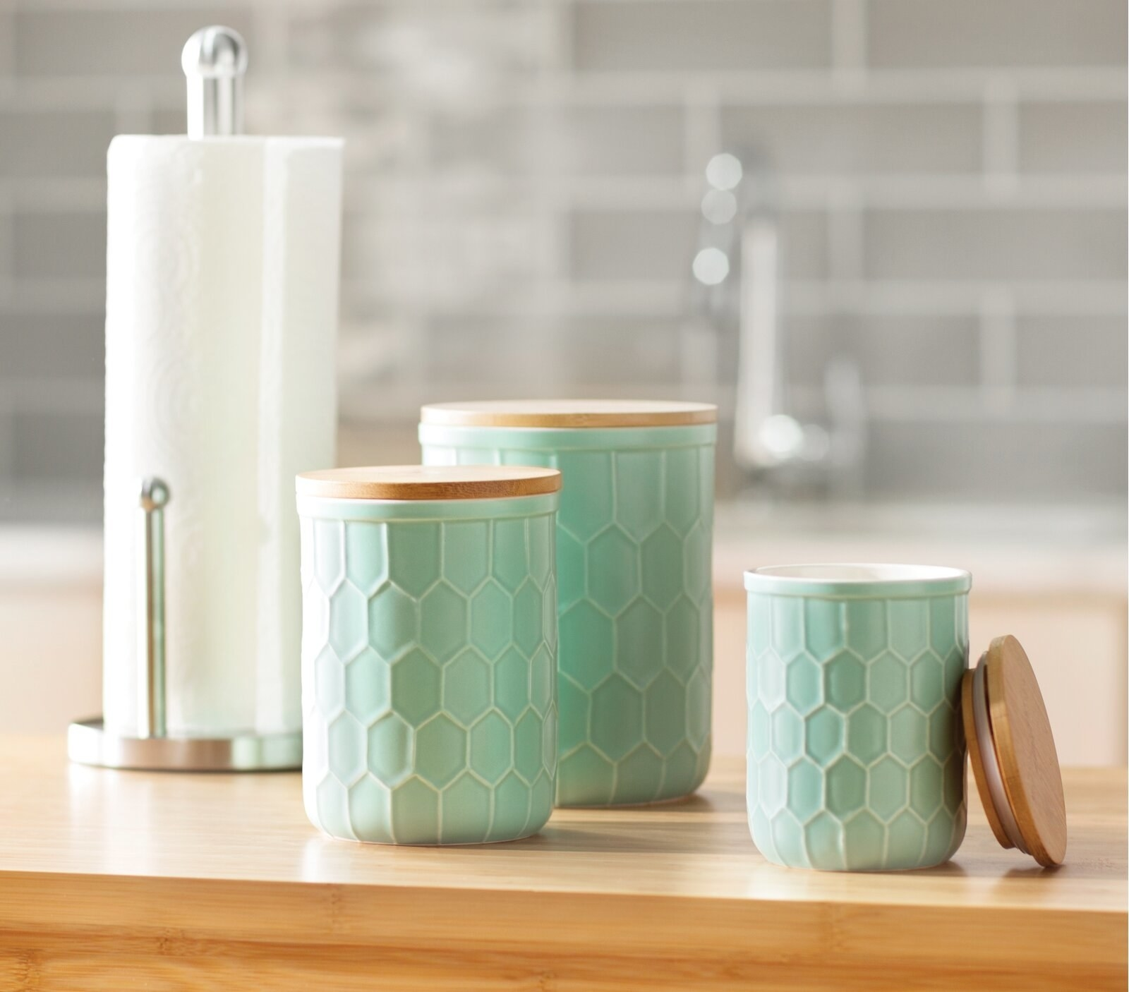 The canisters, which have flat wooden tops and a hexagonal textured pattern on their surfaces, in mint green