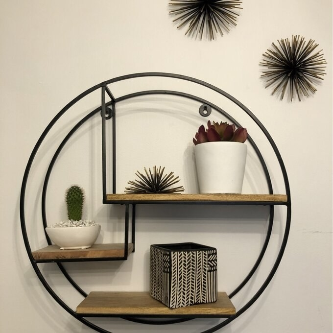 The shelf, which has a frame made of two circular metal tubes, with three wooden shelves staggered within the circle