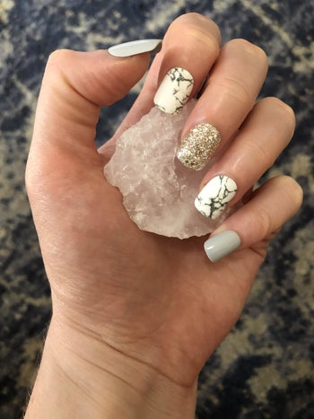 hand with various gray, marble print, and glitter design press on nails