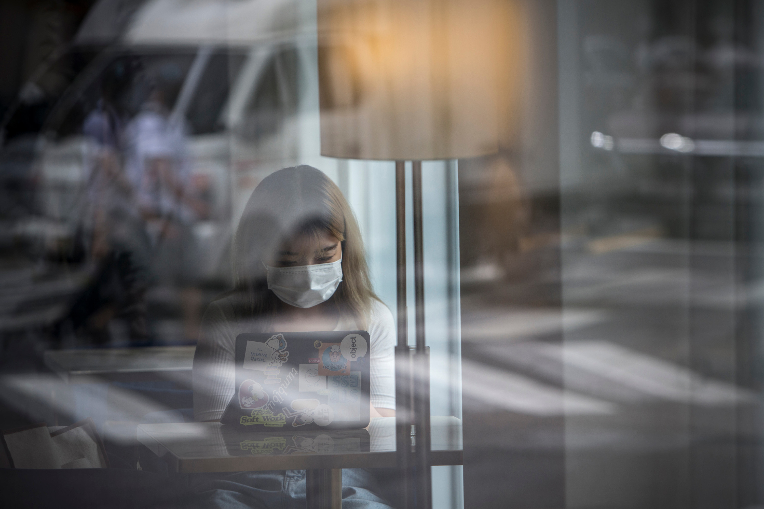 Seen through a window, a woman wearing a face mask sits in a coffee shop in front of her laptop