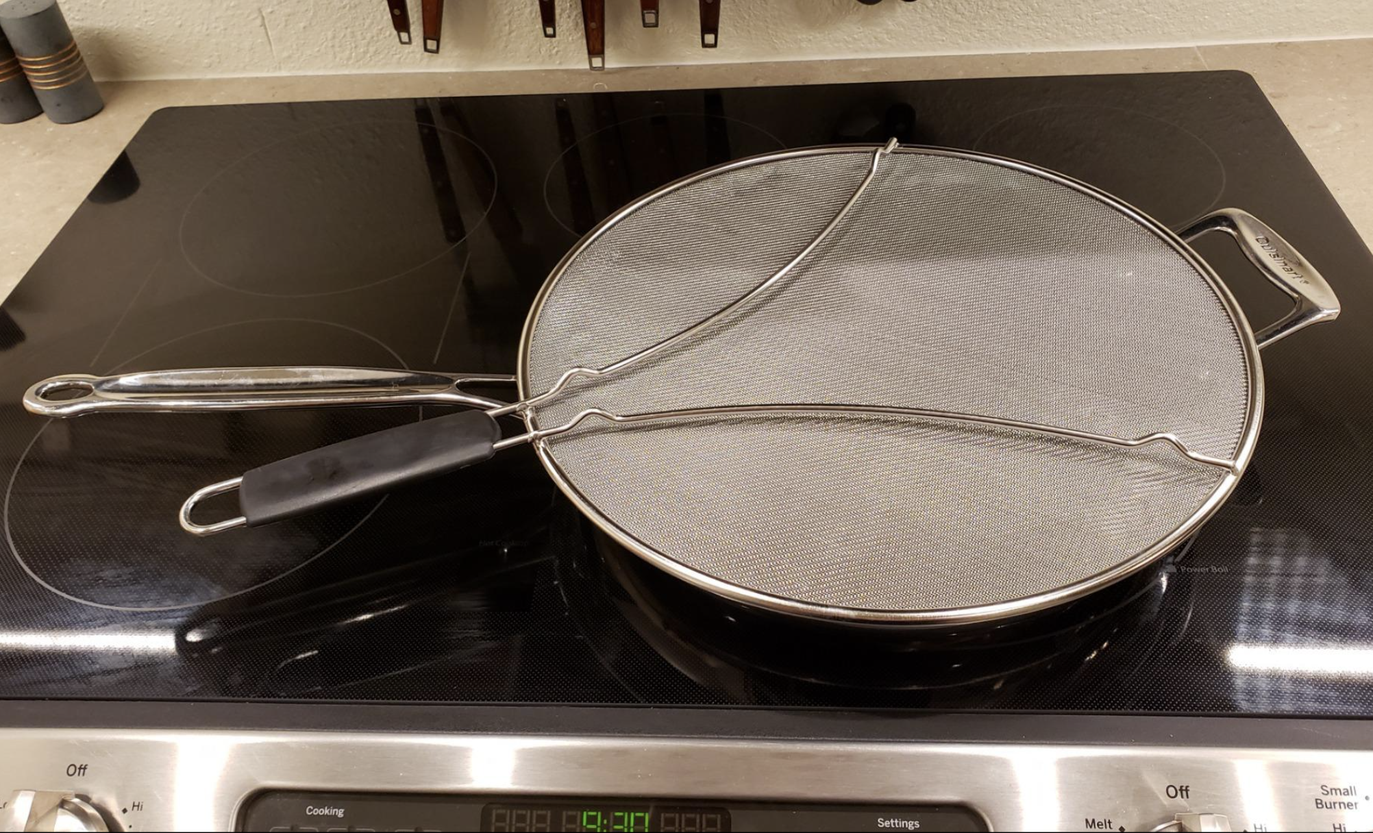 A reviewer photo of a stainless steel splatter guard sitting on top of a pan on a stove