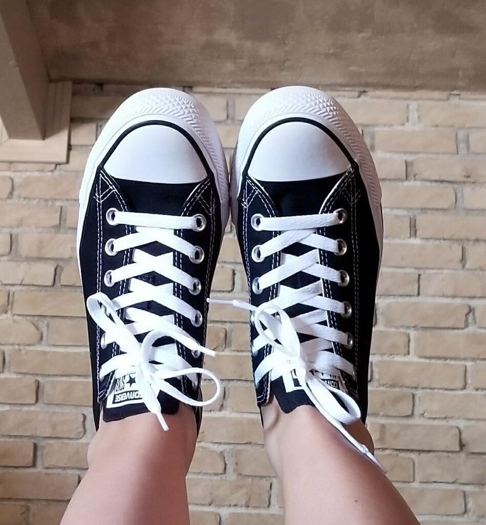 a reviewer in black and white converse