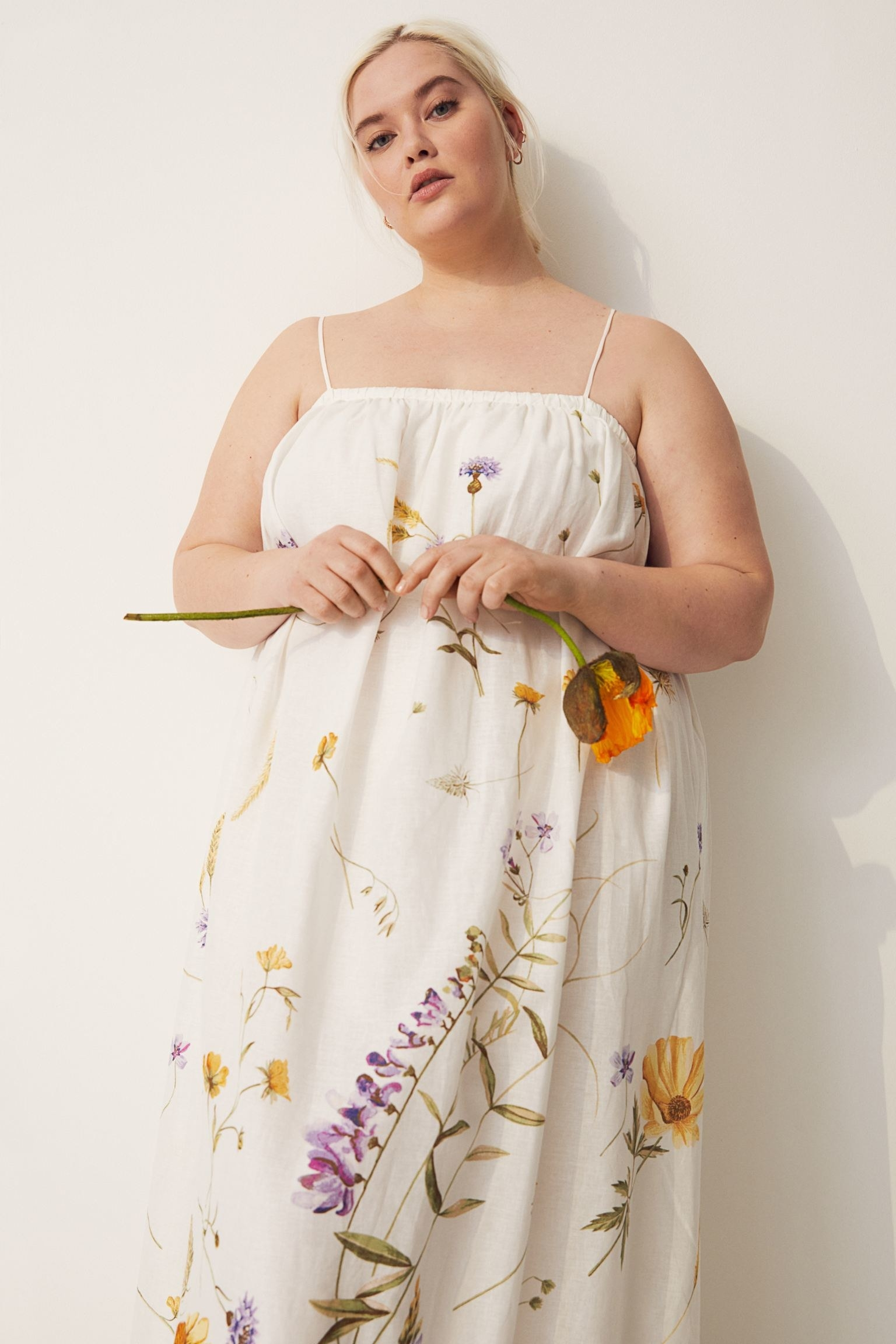 model wearing white dress with floral prints