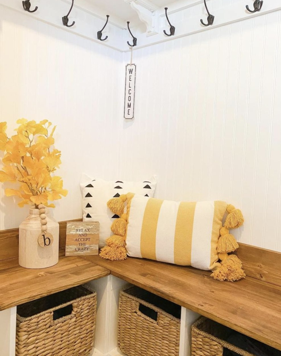 A yellow and white striped throw pillow with tassles