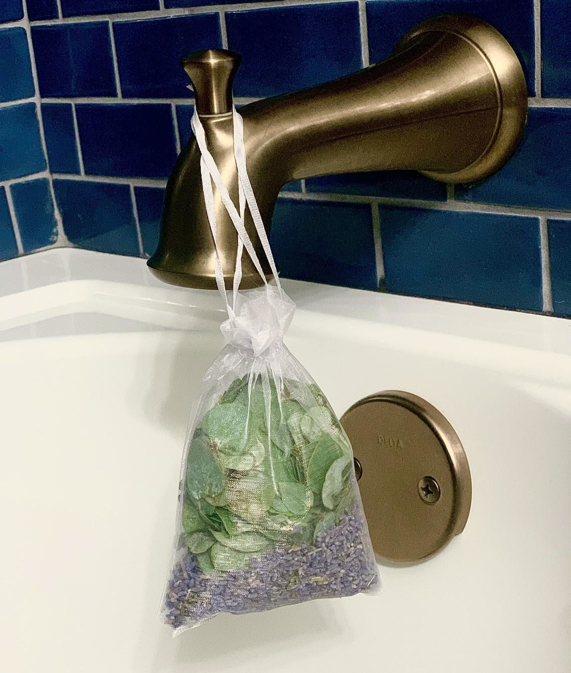A small satchel of lavender and eucalyptus hanging from a bath handle
