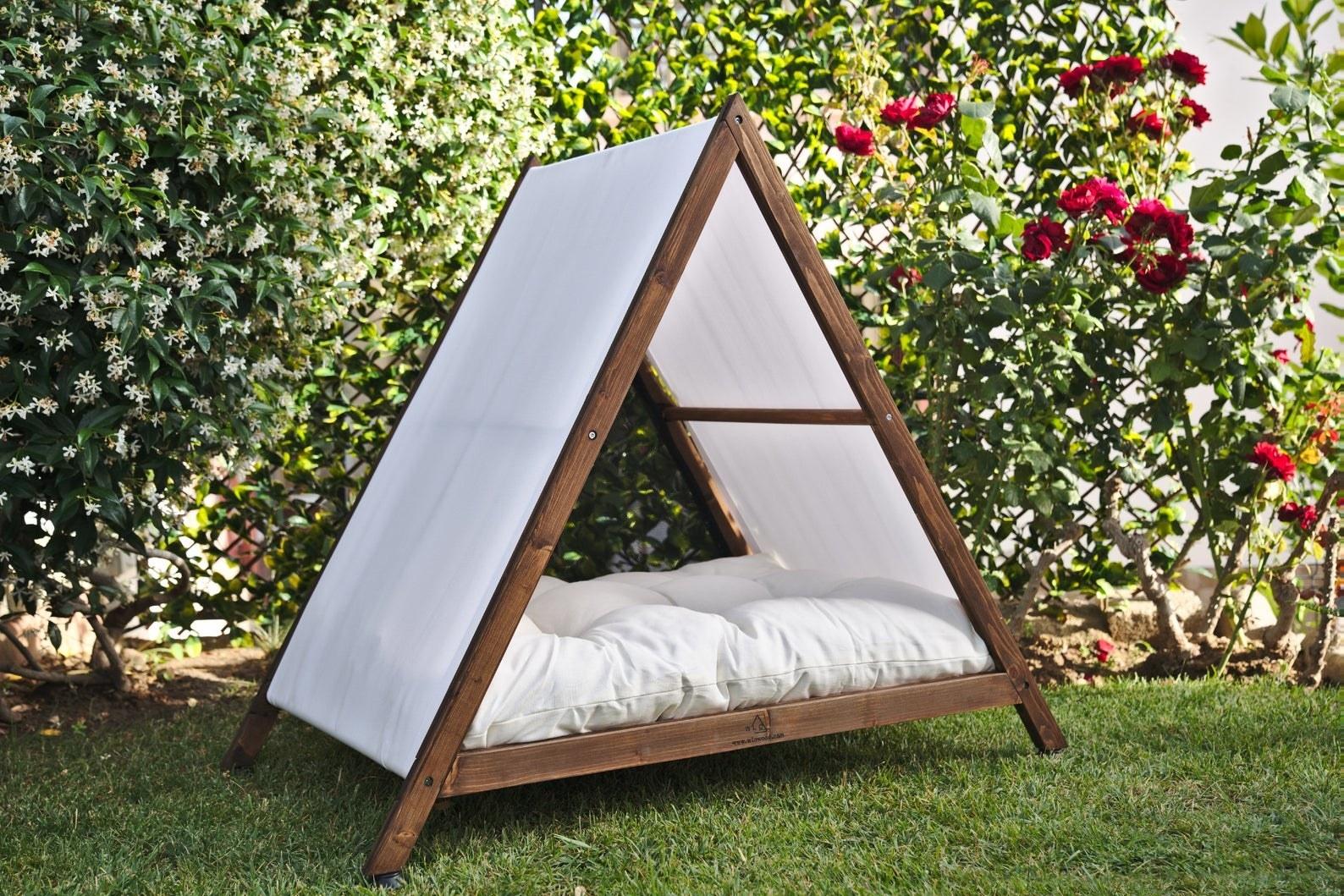 Triangle-shaped dog house with cushion inside