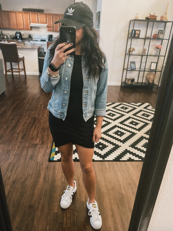 reviewer wearing dress with denim jacket, a baseball cap, and white sneakers