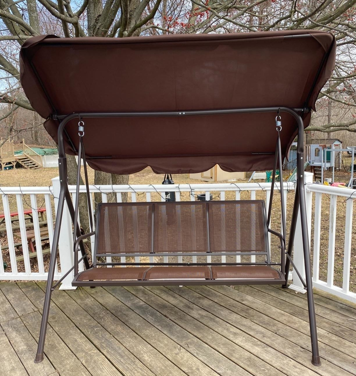 Reviewer photo of their glider in brown on a porch