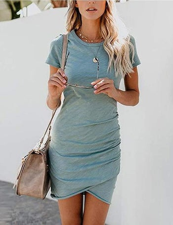 model wearing t-shirt dress styled with necklaces and shoulder bag