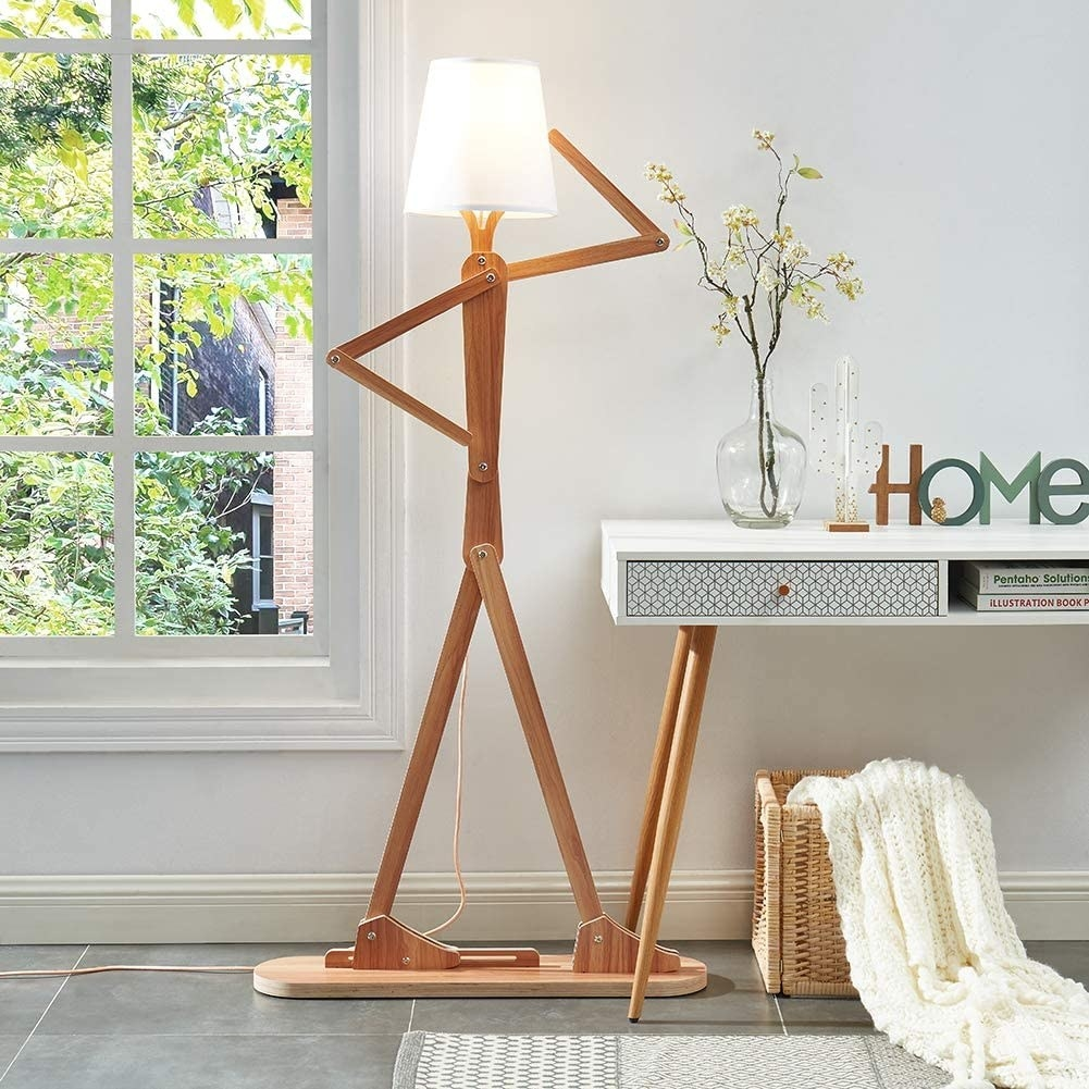 lamp man striking a pose next to a desk with home decor on top