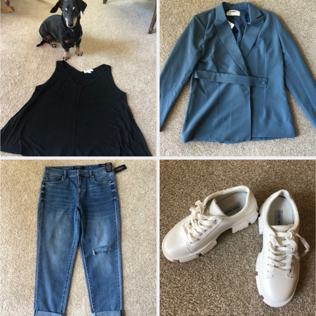 A black tank and dog, a blue jacket, jeans, and sneakers