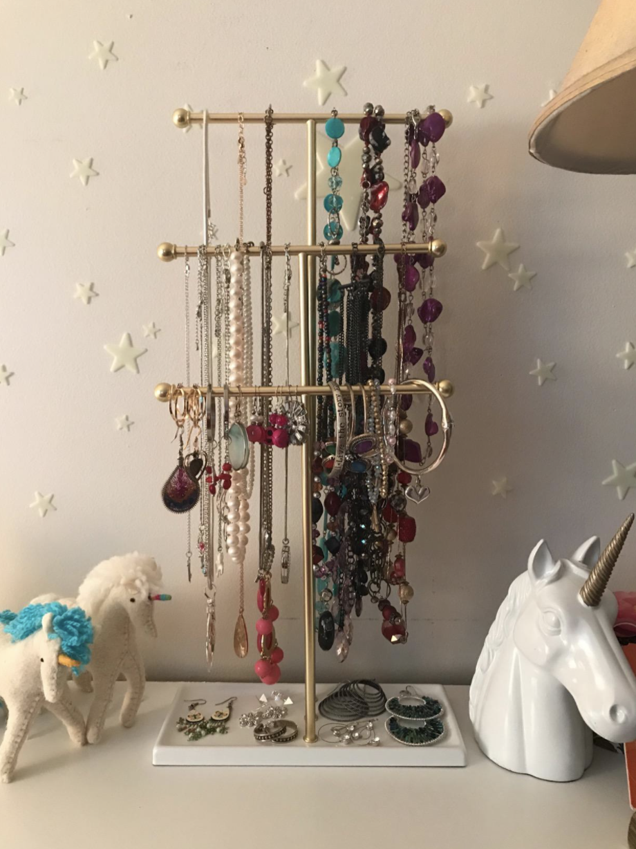 A reviewer photo of gold three-tier jewelry stand with colorful necklaces on the handles and earrings on the bottom