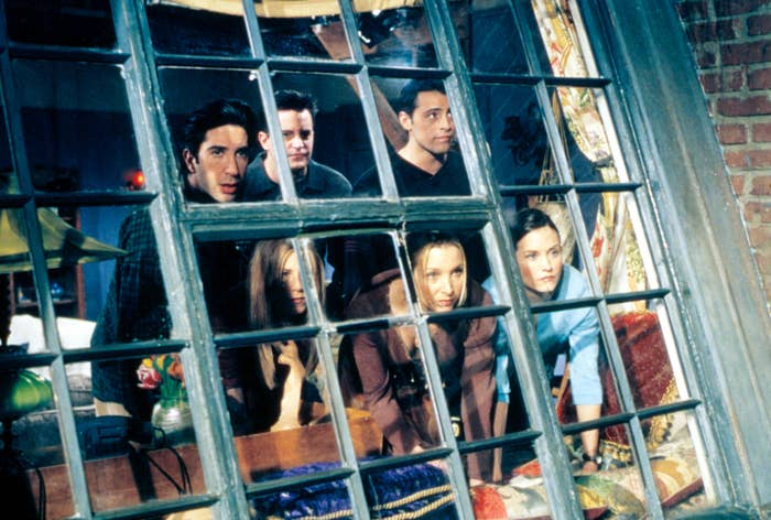 The friends cast looking out a large window