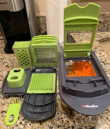 the slicer unit filled with chopped carrots with the lid opening, sitting next to all of the various blade attachments
