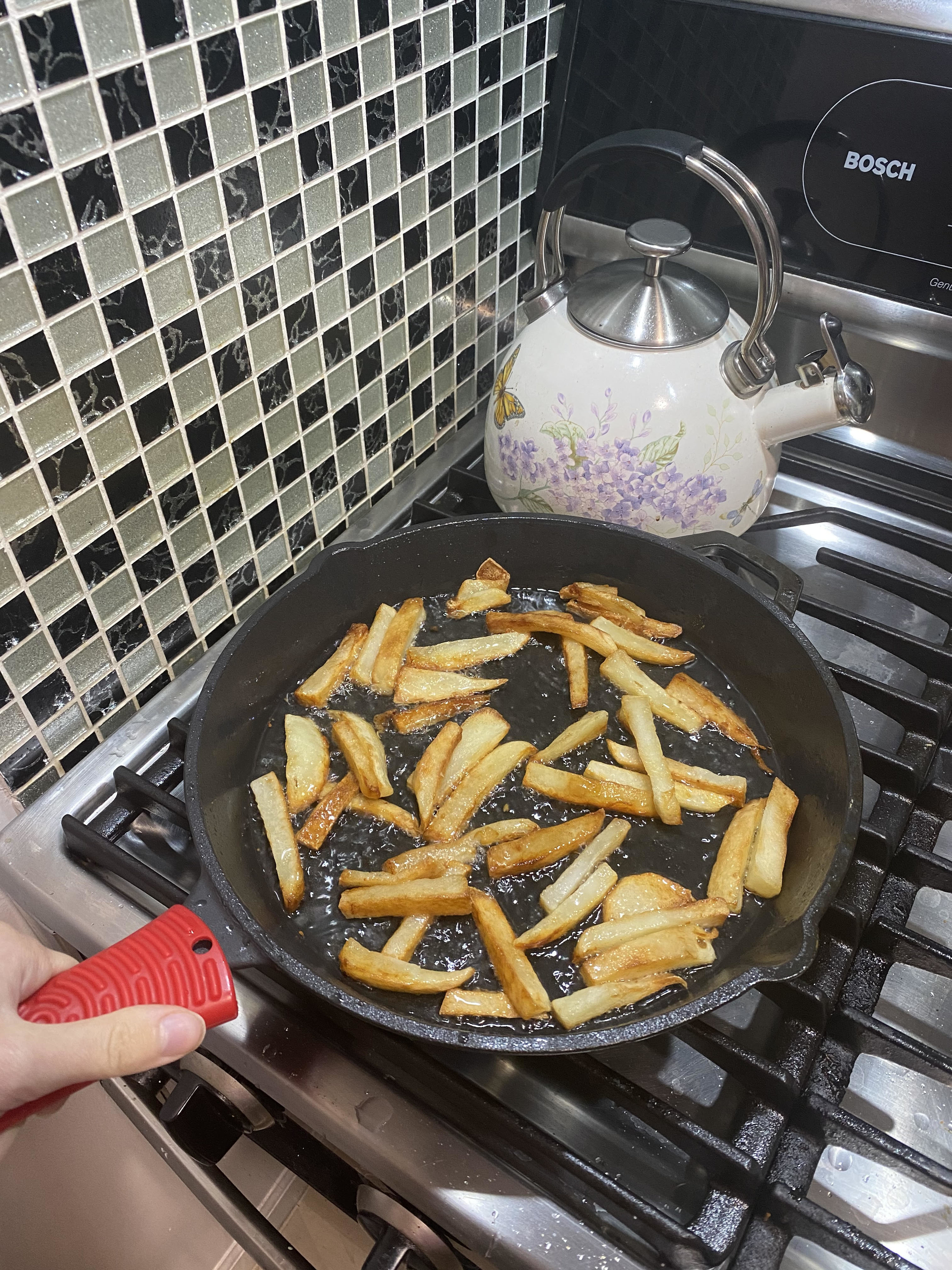 the author using the red handle holder on a cast-iron pan with french fries in it