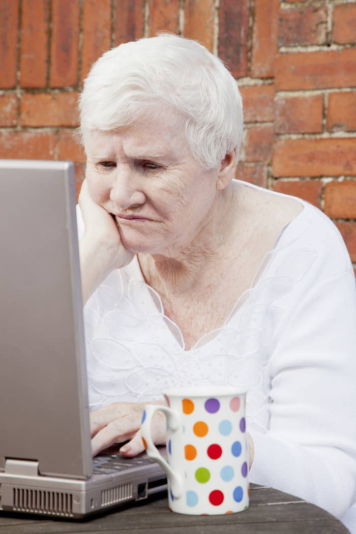 A woman looking at a laptop with a perturbed look on her face