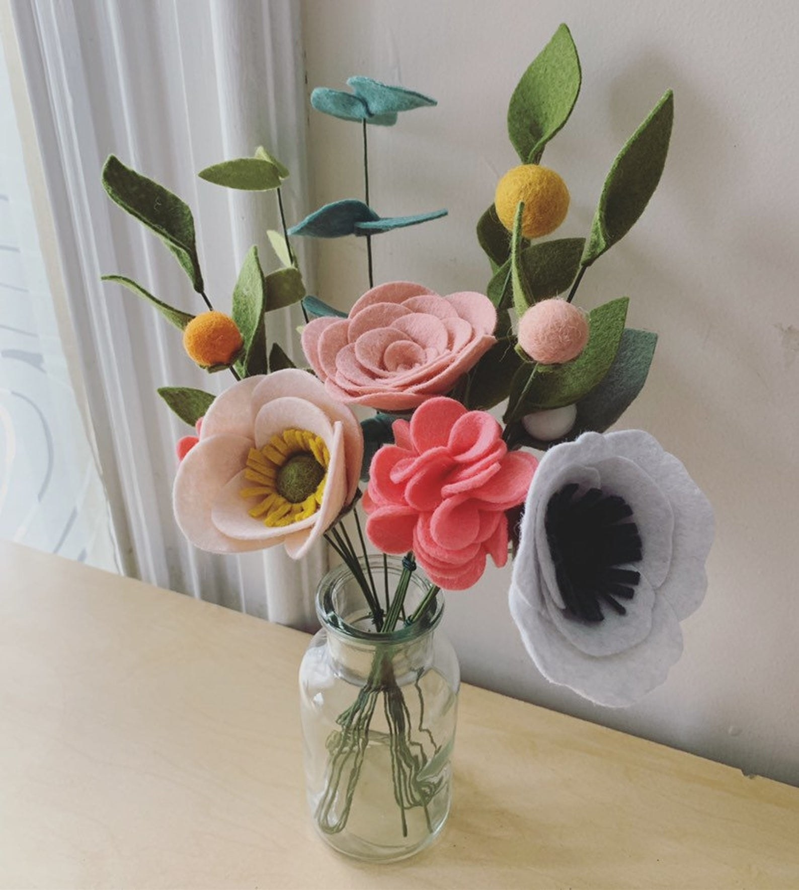 bouquet of colorful felt flowers in a clear jar-like vase