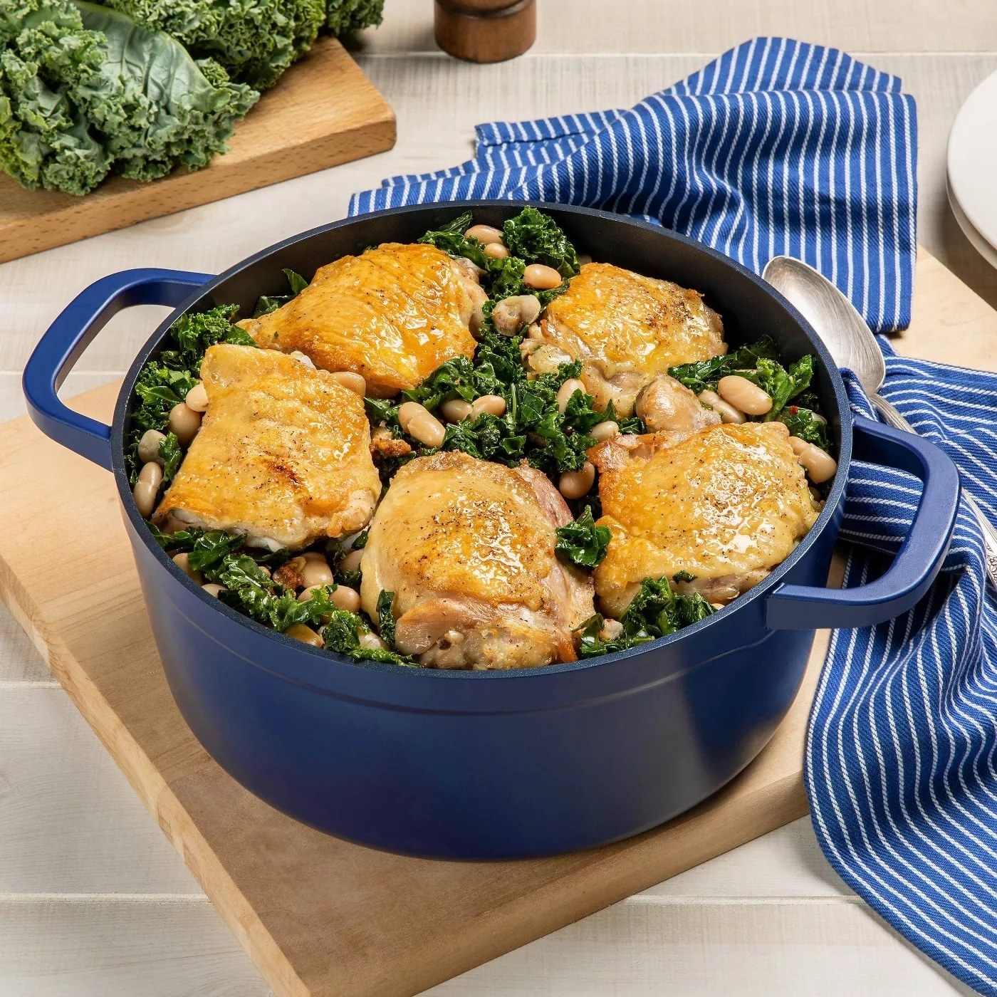 the dutch oven with chicken, greens, and beans inside