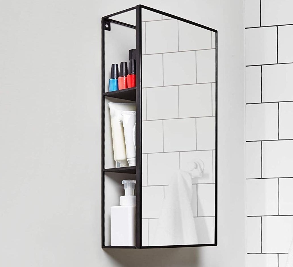 The mirror and cabinet unity in a bathroom with products inside