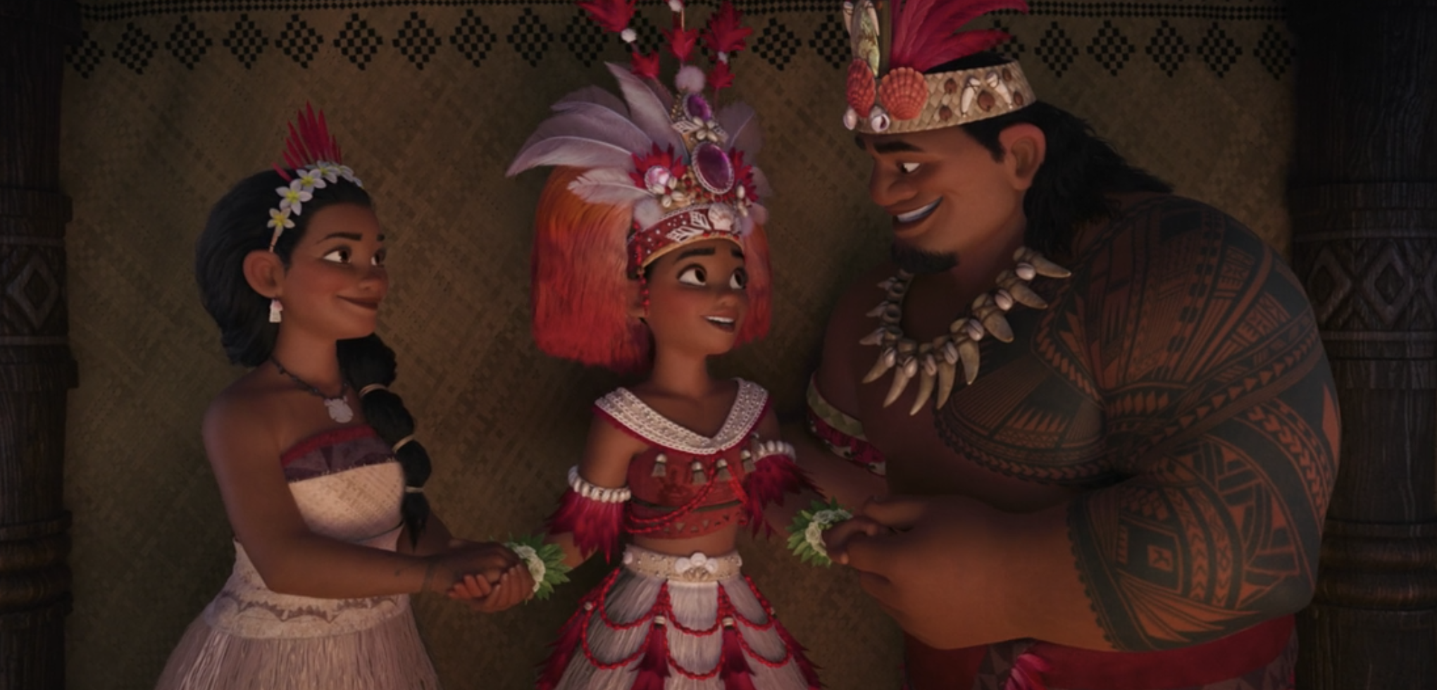 Moana standing with her parents in traditional attire, including a headdress with beads and feathers