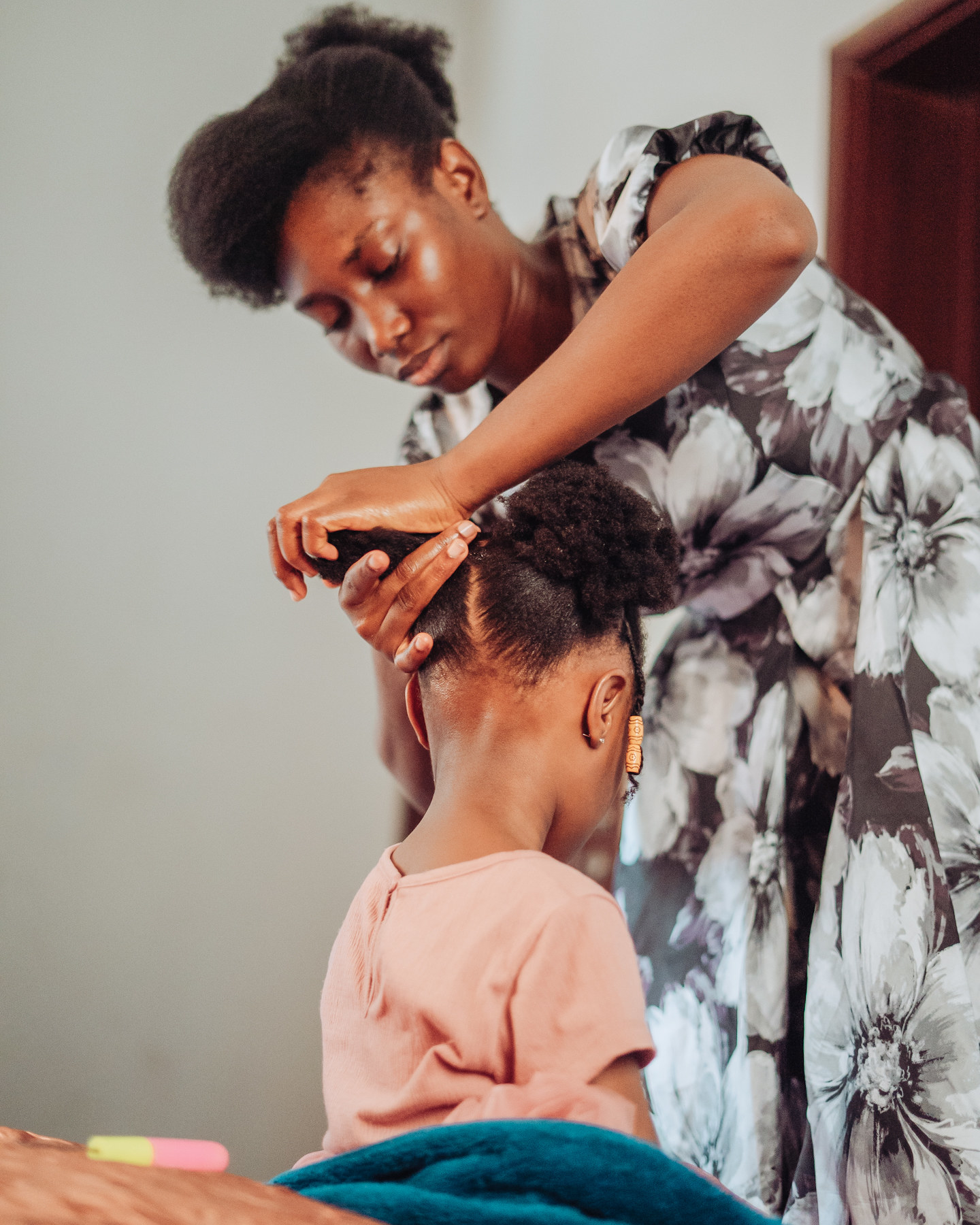 A woman leans over and ties a little girl's hair in a pigtail