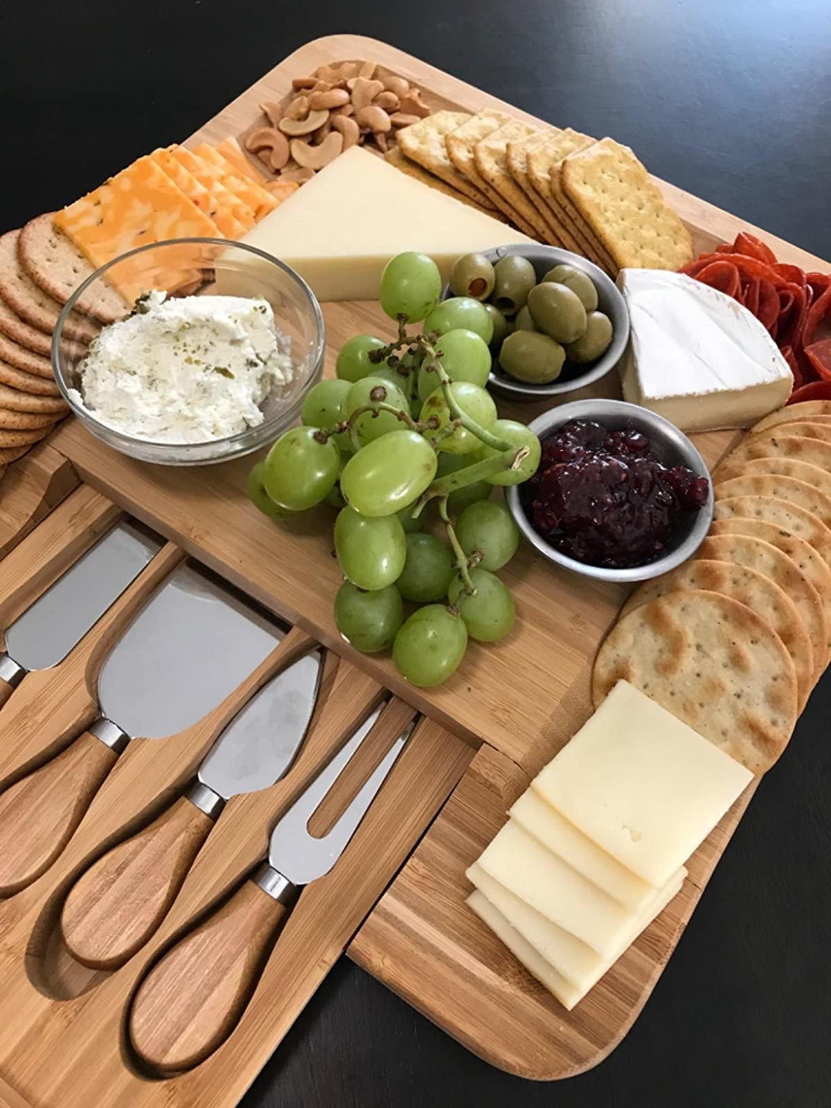reviewer's wooden board with grooves for crackers and a knife drawer that slides out, filled with cheese, crackers, and fruit