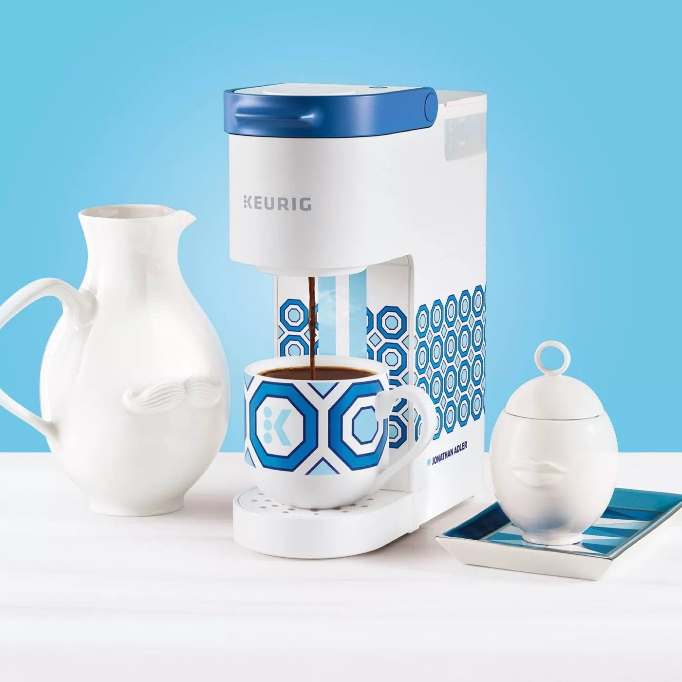 the patterned coffee maker next to white ceramics