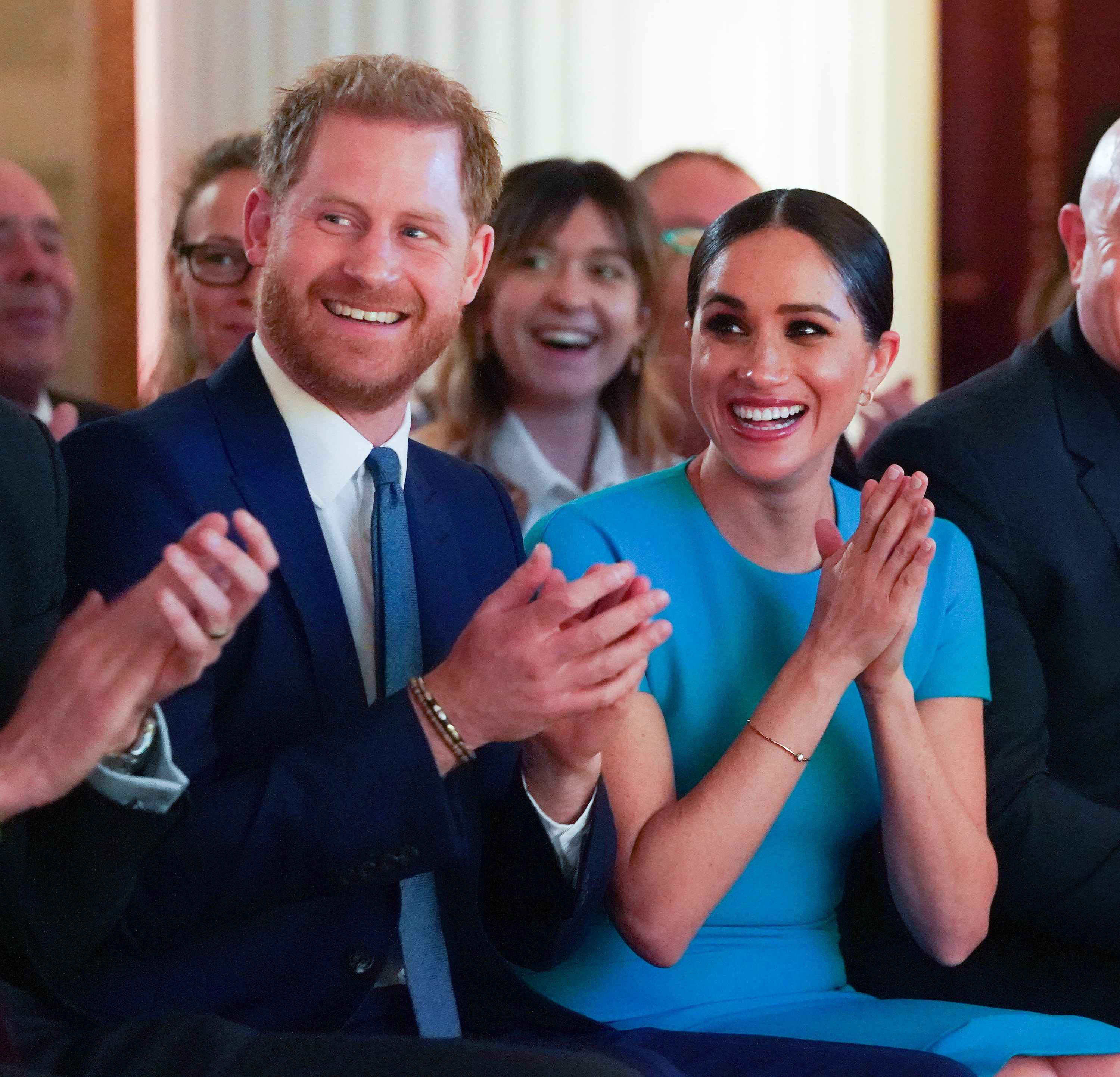 Harry and Meghan applauding and smiling