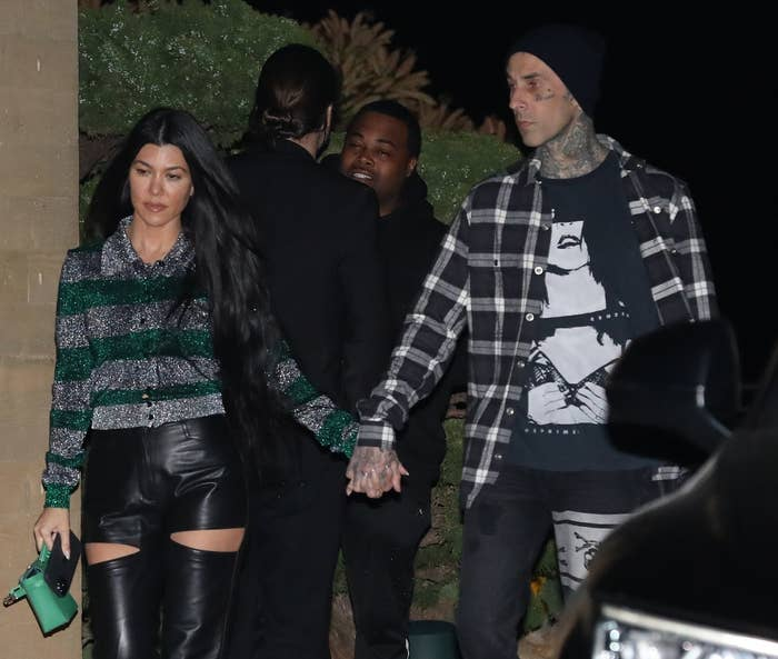 Kourtney and Travis hold hands while leaving a restaurant