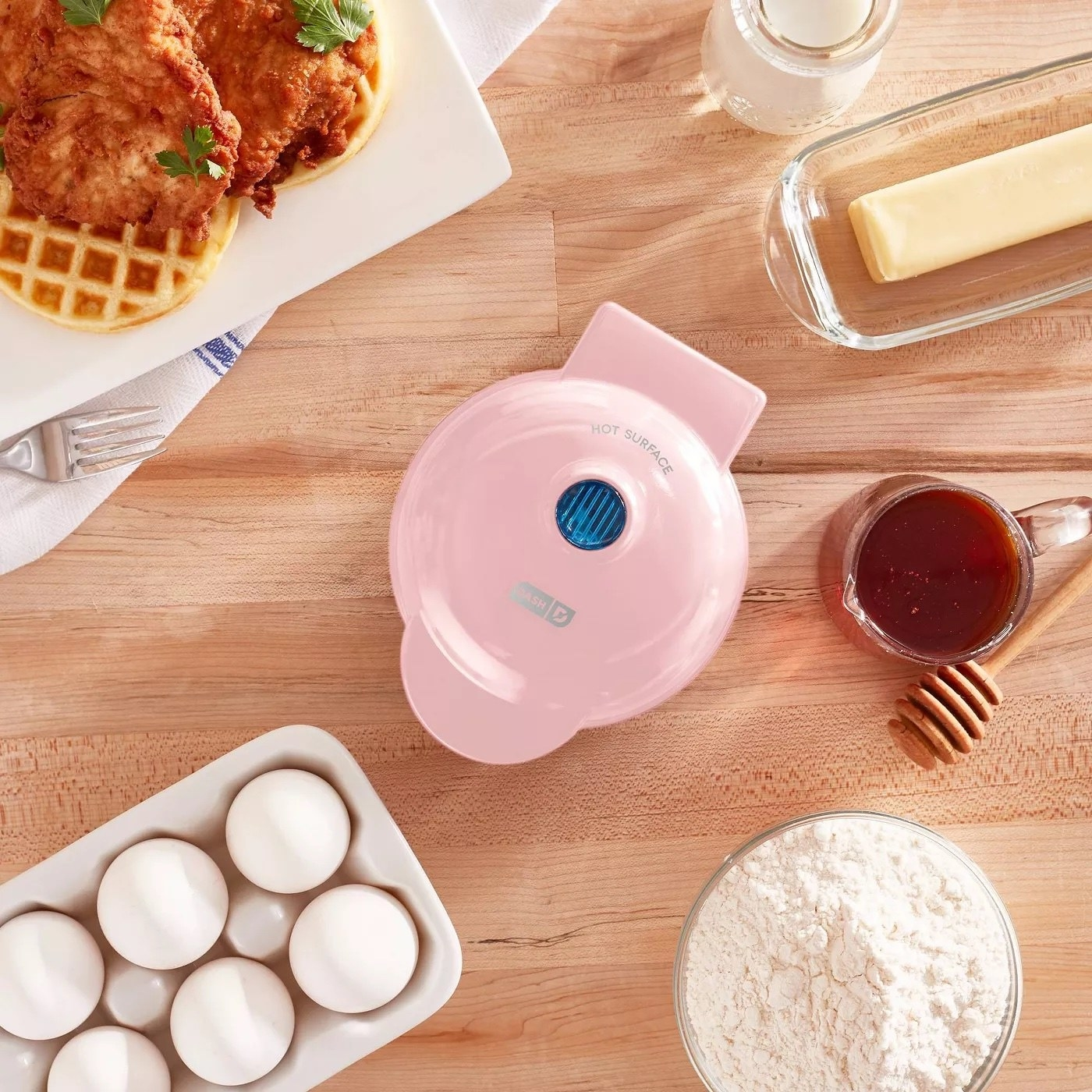 the pink waffle maker surrounded by breakfast supplies