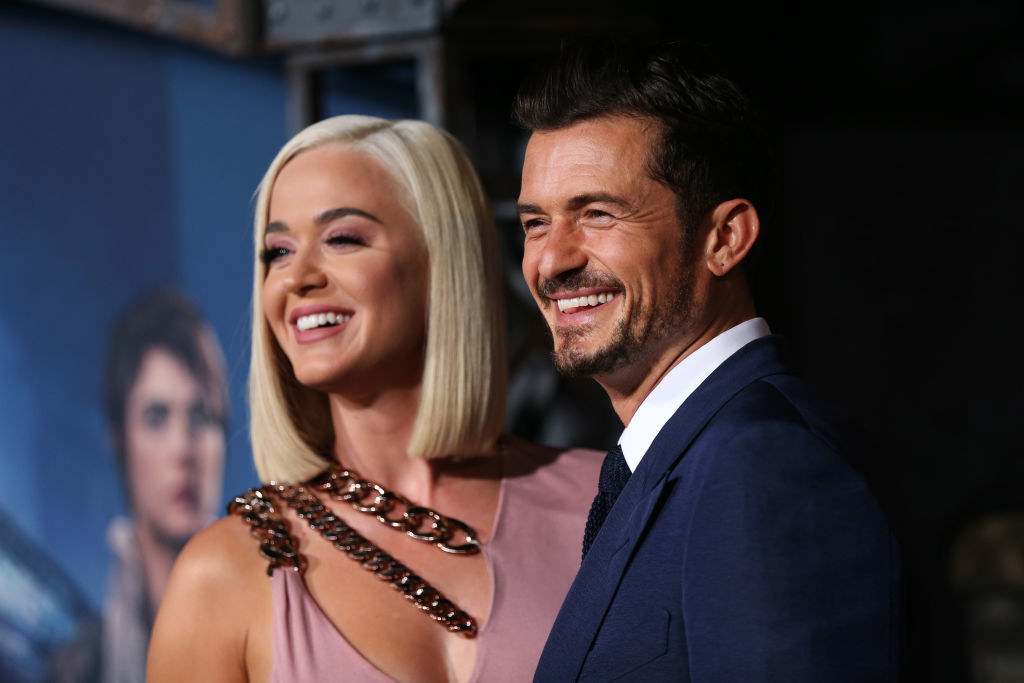 Orlando Bloom and his wife Katy Perry smiling at a red carpet event