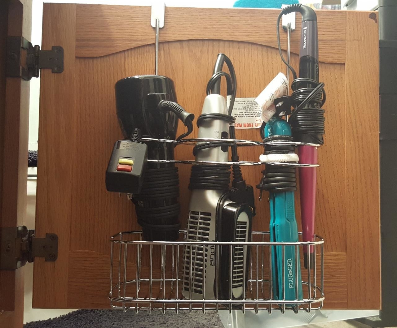 A reviewer photo of a hair tool organizer attached to the inside of a cabinet door holding a blow dryer, hot air brush, a hair straightener, and a curling wand