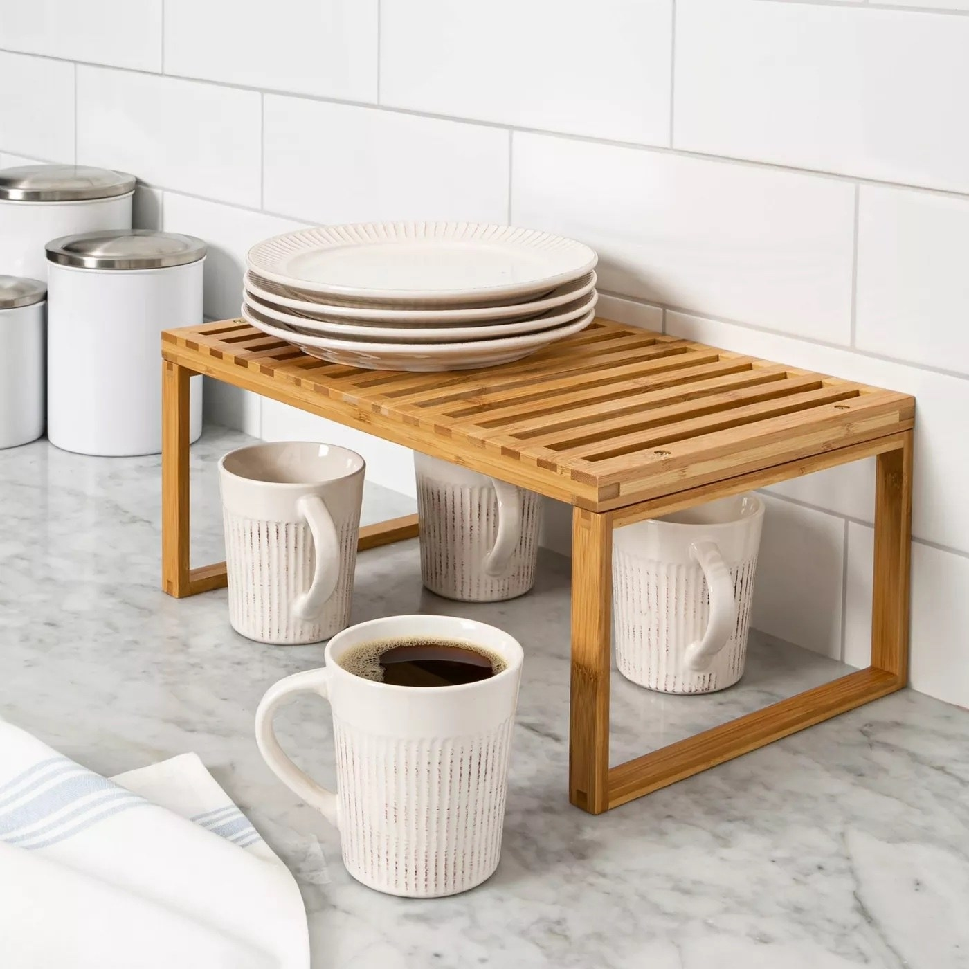 the shelf on a counter with coffee cups and plates