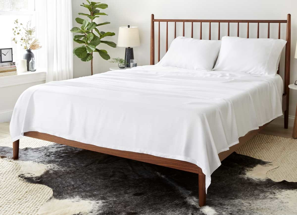 the white arctic aire sheet set on a wooden bed