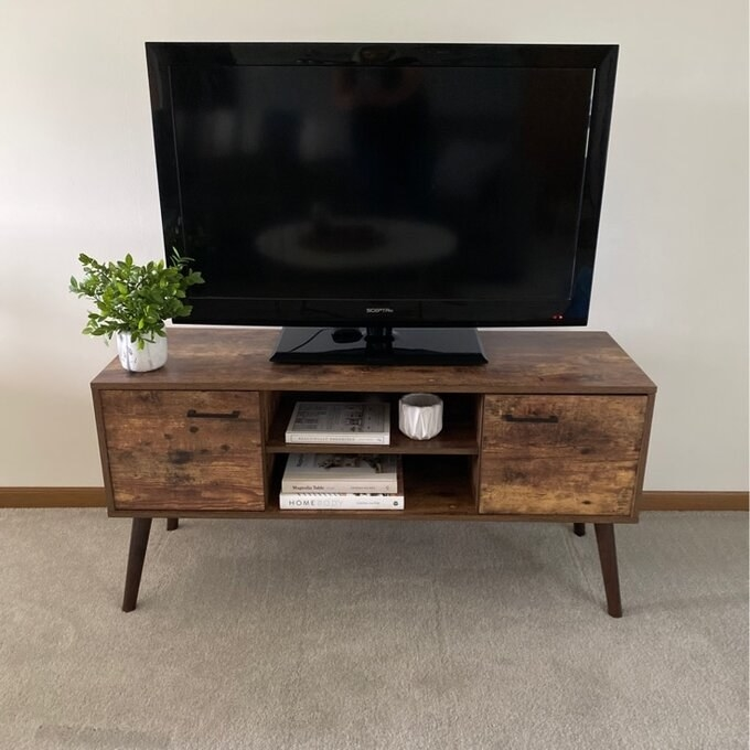 The TV stand, which has an open storage area in the center with two shelves, and a closed cubby at either end