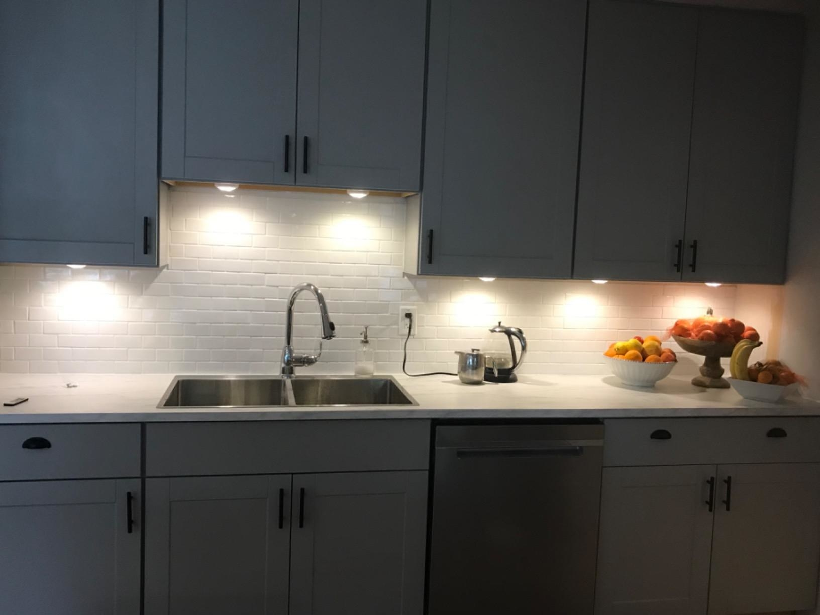 reviewer photo of a gray kitchen with multiple puck lights lighting up the counter underneath the cabinets