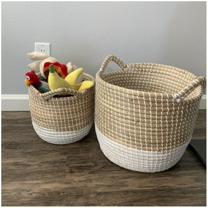 The baskets, which have a white woven bottom and a light brown woven top, are round, and have two round handles for carrying extending from the top edge of the basket