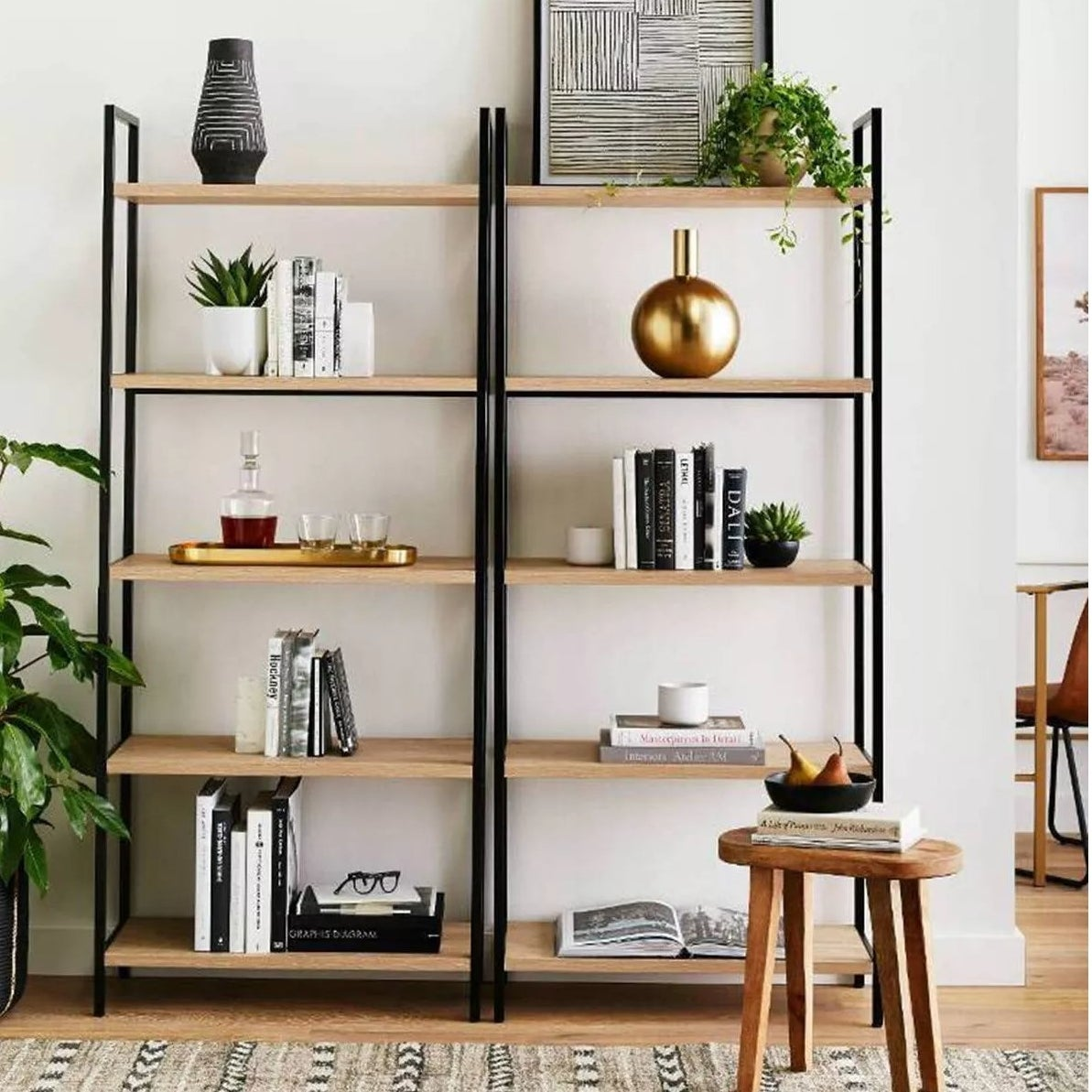 The ladder bookshelf with a metal frame and light wooden shelves in a living room