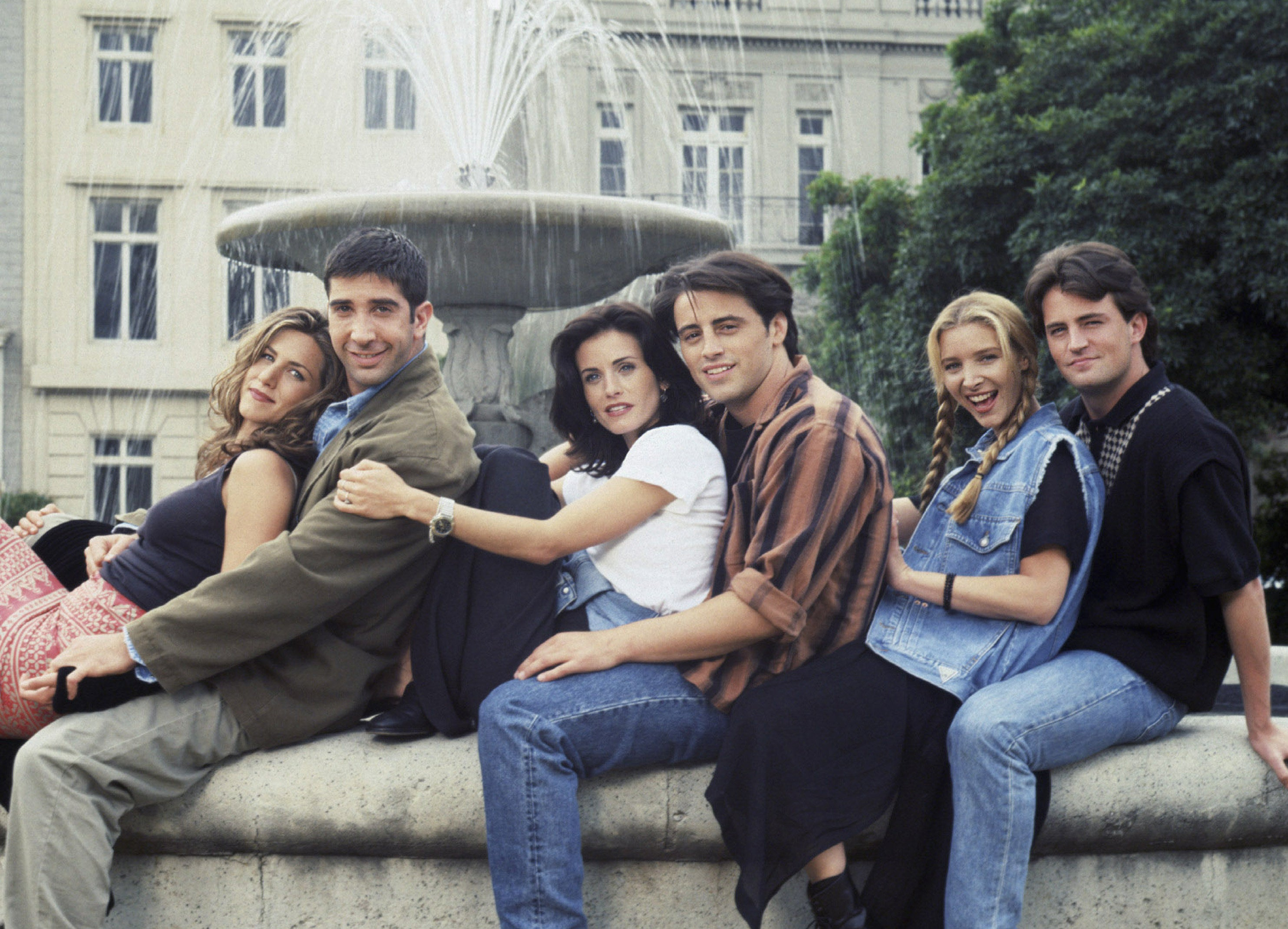 The Friends cast sit together on the edge of a fountain