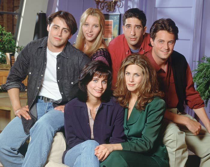 The Friends cast pose on a couch together