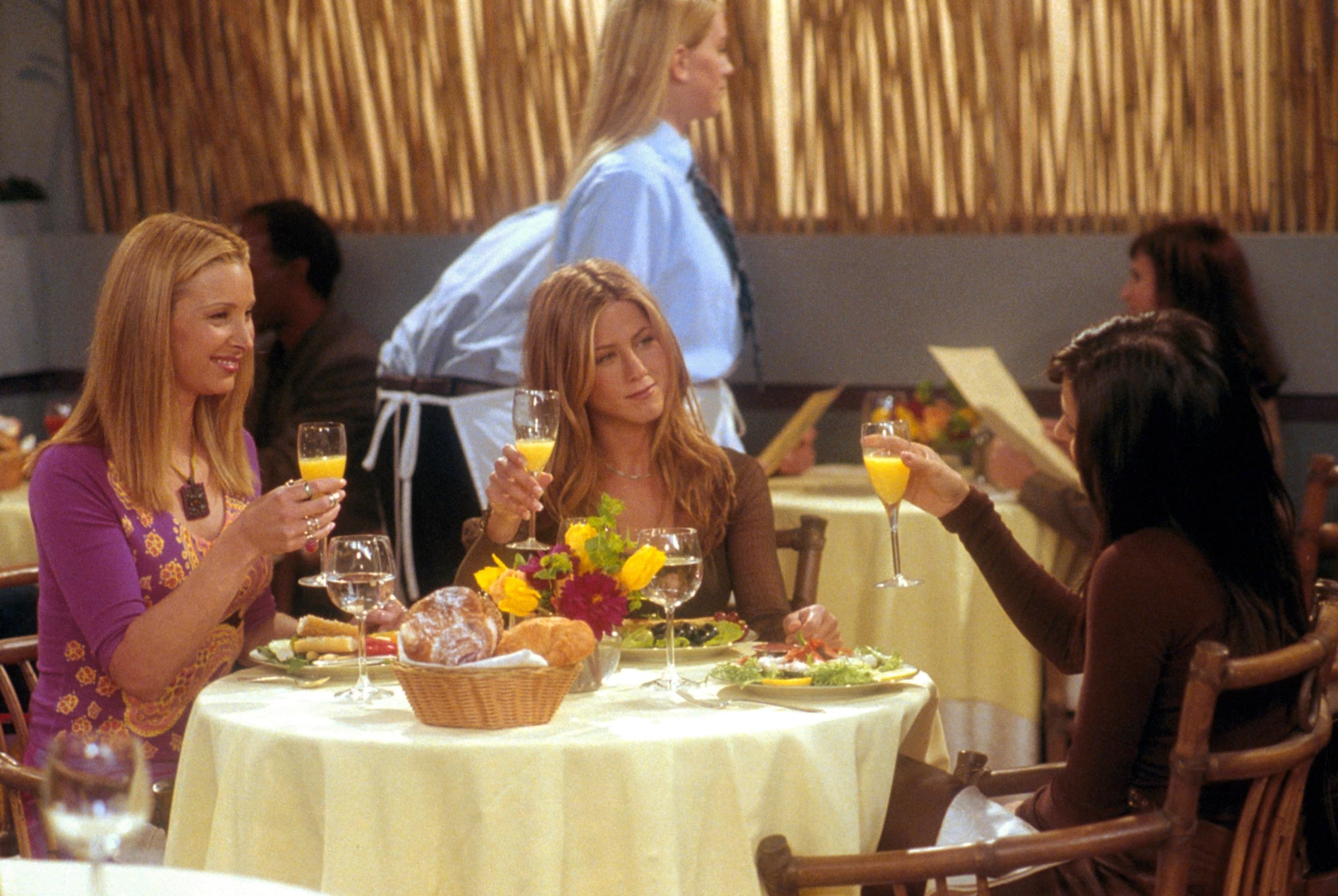 Lisa and Jennifer sit at a table at a restaurant on an episode of Friends