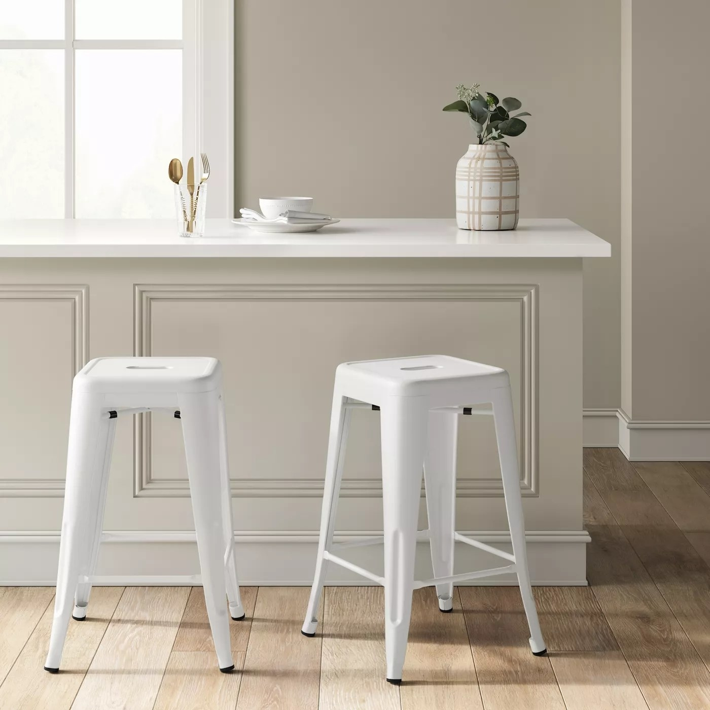 two white barstools in front of a kitchen island