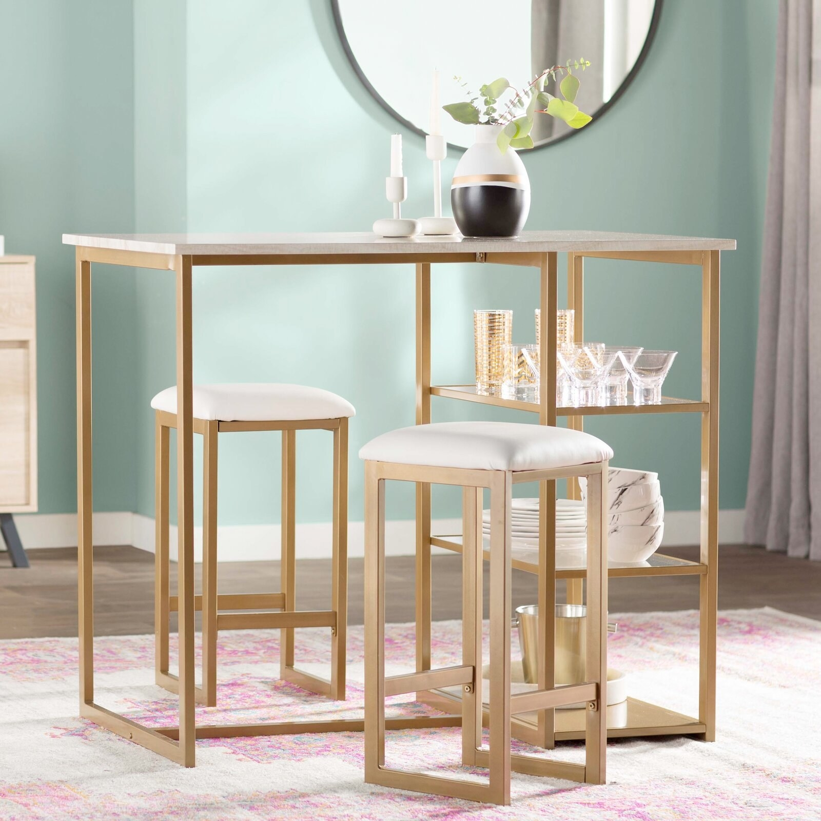 The dining set, which includes two square-cushioned stools and a rectangular table on high legs
