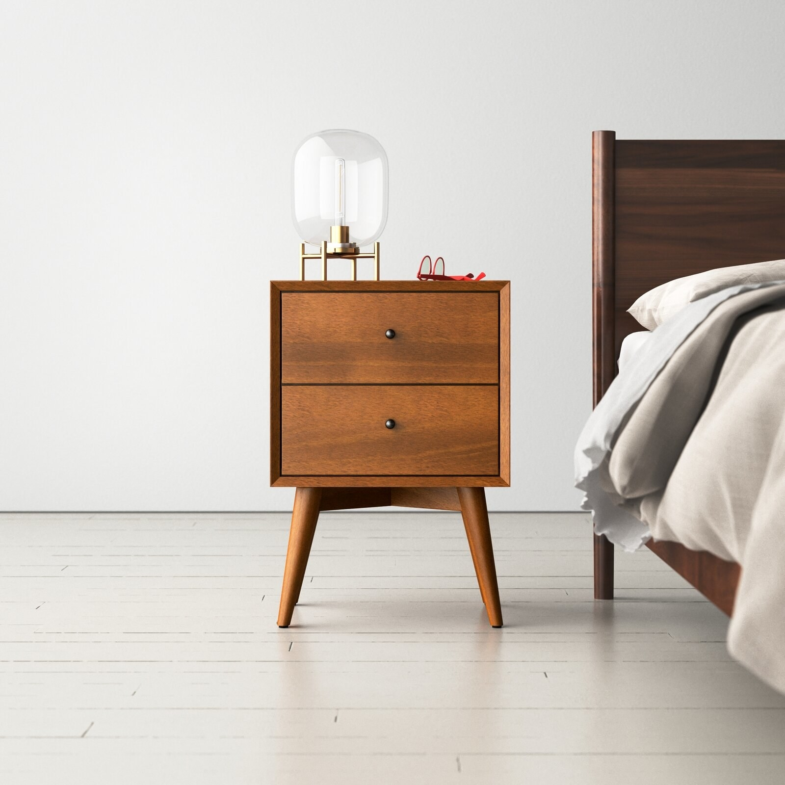 The nightstand, which has two drawers with small knob pulls and four splayed legs
