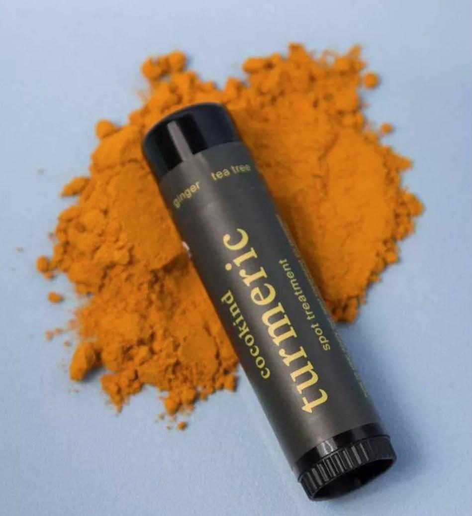 Cocokind turmeric spot treatment lying against turmeric powder
